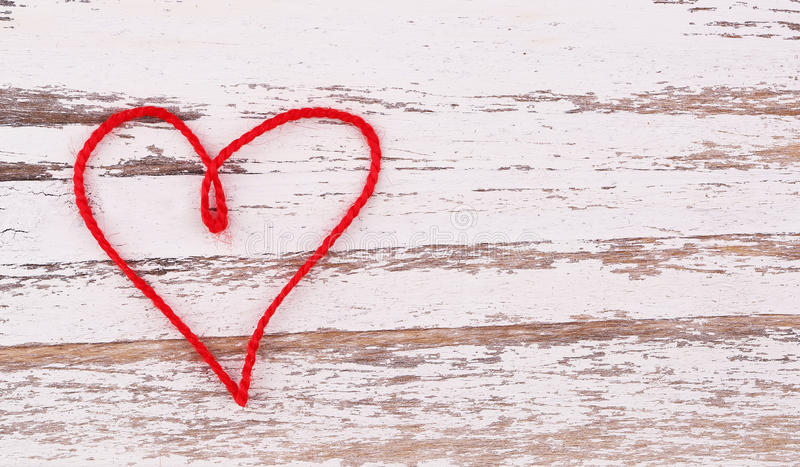 Valentine's Day. Red heart of thread shaped on wood background stock photos