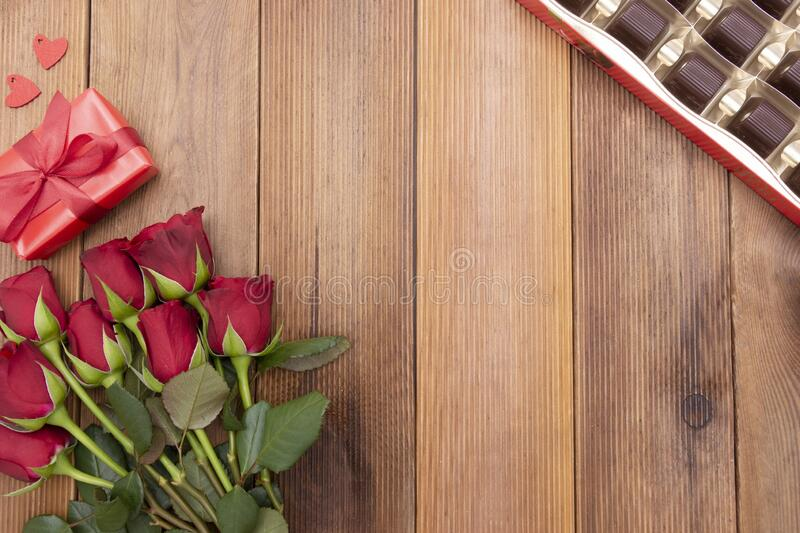 Valentine's Day, red roses, gift boxes and chocolate box with ribbon, over wooden background flat lay, birthday abstract. Background with copy space for royalty free stock photography