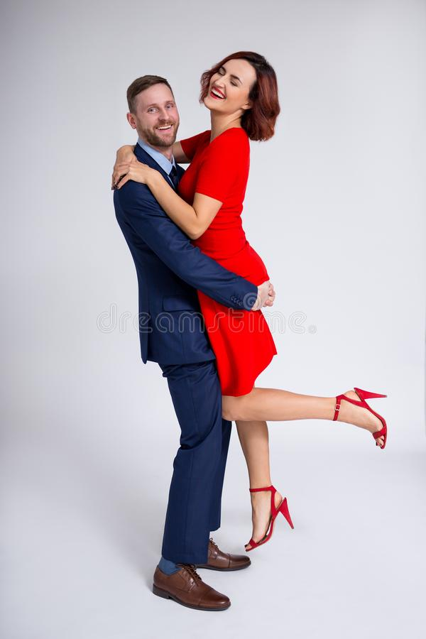 Valentine`s day and relationship concept - full length portrait of handsome man holding beautiful woman in his hands over white stock images
