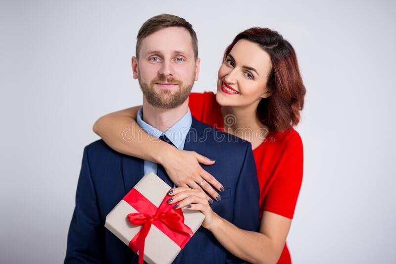 Valentine`s day, relationship and love concept - beautiful woman embracing her boyfriend and holding gift box over white royalty free stock image
