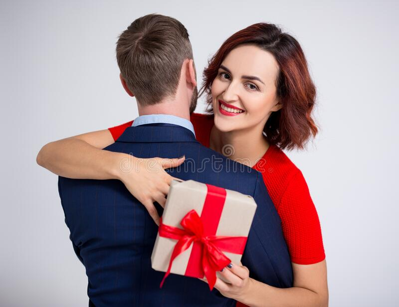 Valentine`s day, relationship and love concept - portrait of woman embracing her boyfriend and holding gift box over white stock photo