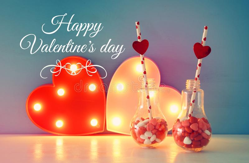 Valentine& x27;s day romantic background with plastic light bulb with heart shape sweet candies on white table. royalty free stock photo