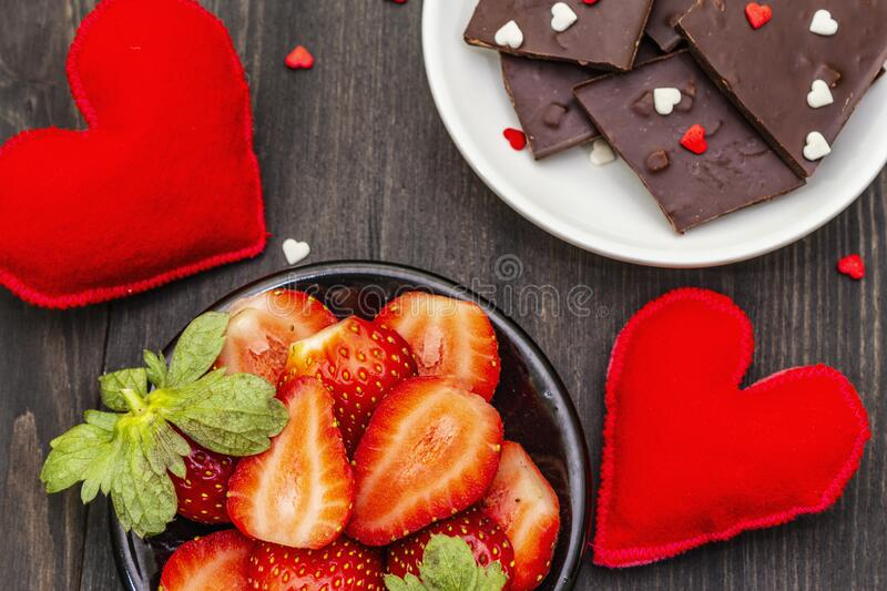 Valentine`s Day romantic concept. Chocolate, fresh ripe strawberry, red felt hearts. Sweet dessert for lovers. Black wooden. Background, top view, close up royalty free stock photography
