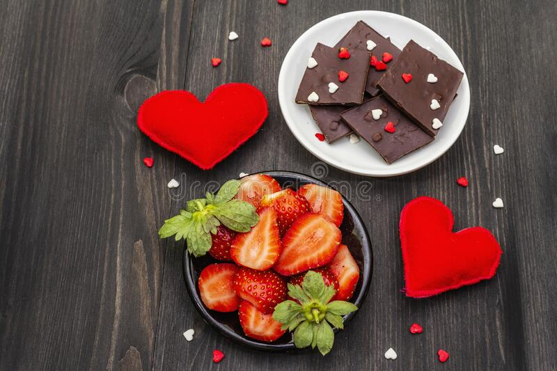 Valentine`s Day romantic concept. Chocolate, fresh ripe strawberry, red felt hearts. Sweet dessert for lovers. Black wooden royalty free stock photography