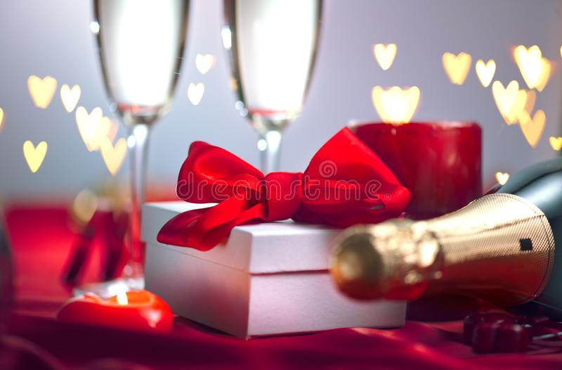 Valentine`s Day romantic dinner. Champagne, candles and gift box over holiday background royalty free stock photo