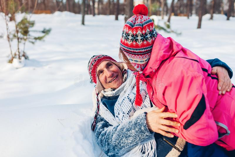 Valentine`s Day. Senior couple hugging in winter forest. Man and woman lying in snow and having fun royalty free stock image