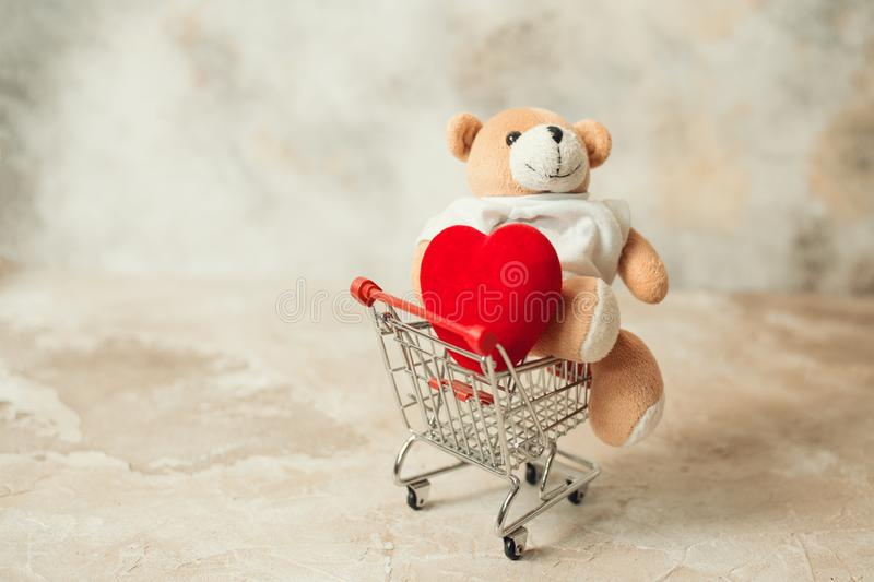Valentine`s Day shopping concept. White heart and gift with red ribbon royalty free stock photo
