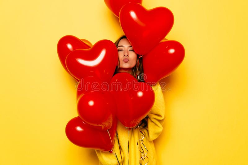 Beautiful girl giving a kiss looking out of heart shaped air balloons. Valentine`s day. Smiling girl in yellow sweater giving a kiss, looking out of bunch of red royalty free stock photos