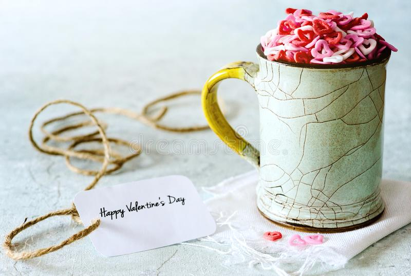 Valentine`s day: sugar candies of hearts in a cup on delicate background. Sugar shapes of hearts in a cup on delicate background, with greeting card stock photo