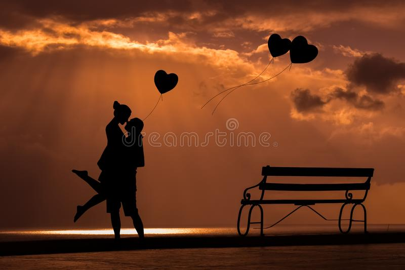 Valentine`s Day sunset background with couple and heart balloons royalty free stock photo