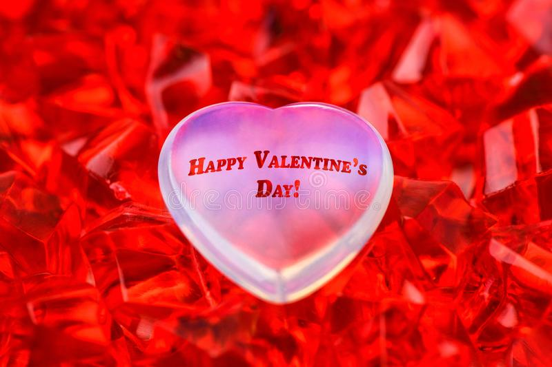 Valentine`s day. White glass heart lies on red ruby crystals close-up on it inscription happy Valentine`s day. Macro photograph stock image