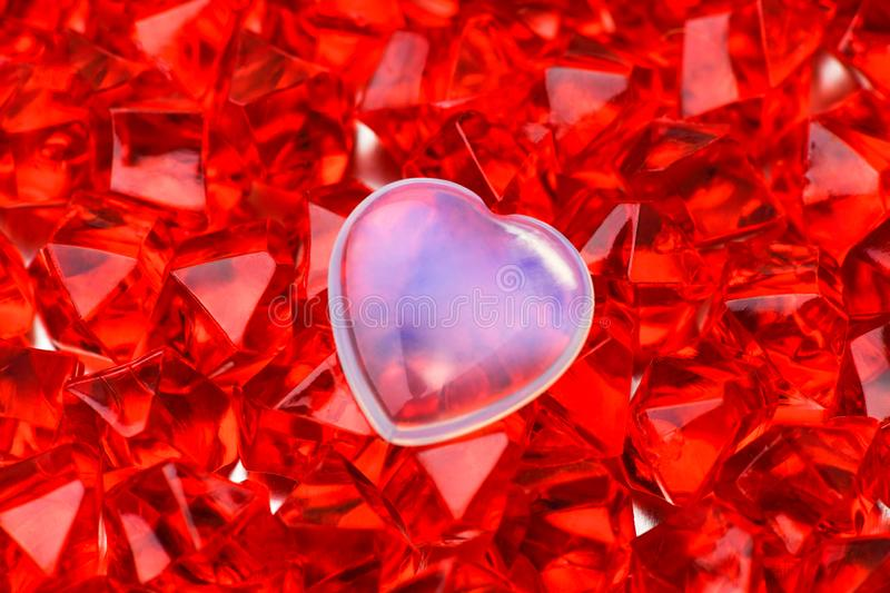 .Valentine`s day. A white glass heart lies on red-ruby crystals in the middle. Macro photography royalty free stock photos