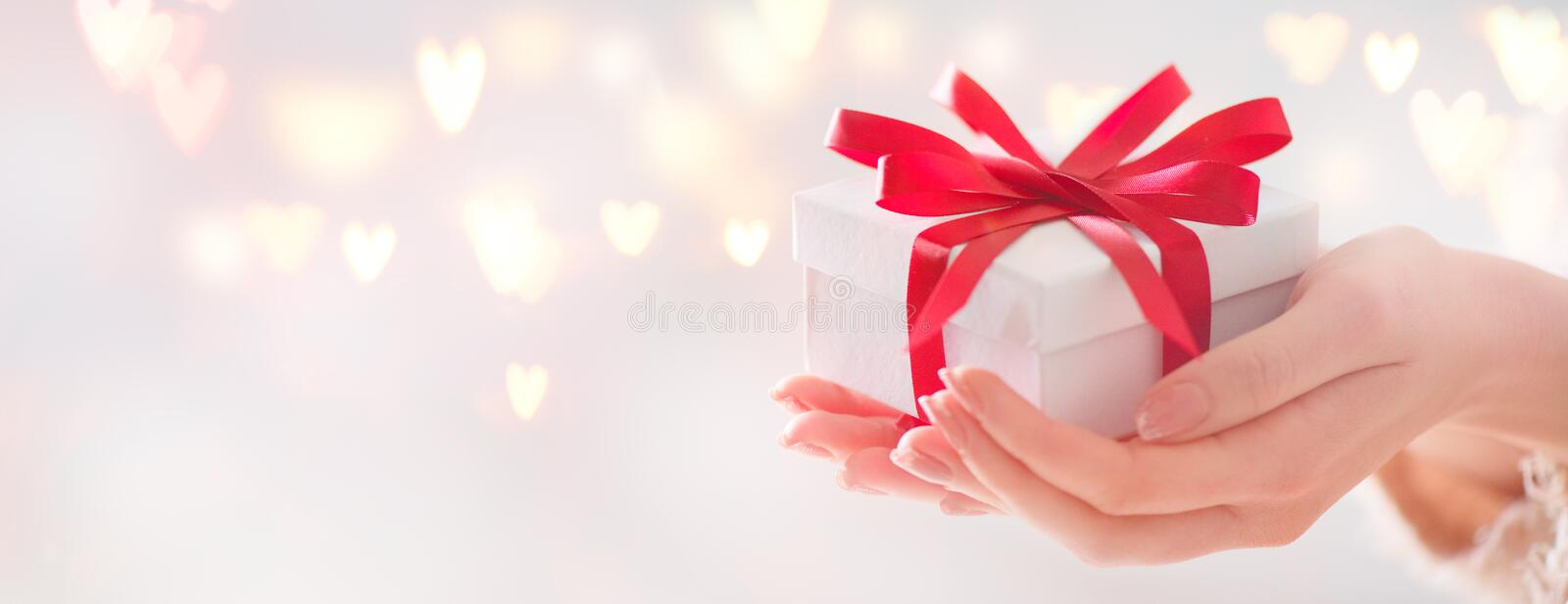 Valentine`s Day. Woman holding gift box with red bow. Over holiday background stock photos