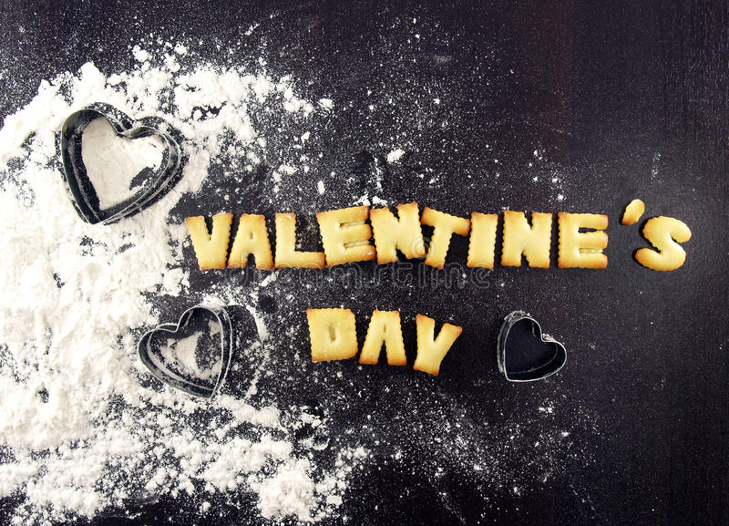 valentine's day text, biscuit cookies letters with heart shaped cookie cutter and sprinkled wheat flour stock photos