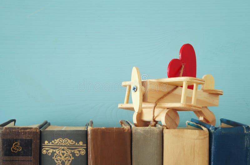 Valentine& x27; s dnia tło Drewniany zabawka samolot z sercem nad starymi książkami fotografia stock