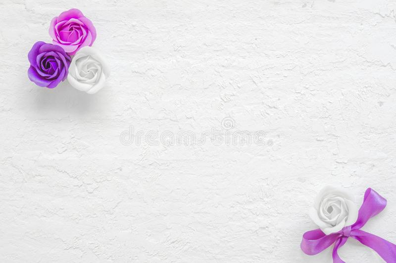 Valentine& x27;s flat lay mockup. Beautiful pink and violet rose flowers on grunge white wooden background with copy space. Styled stock images