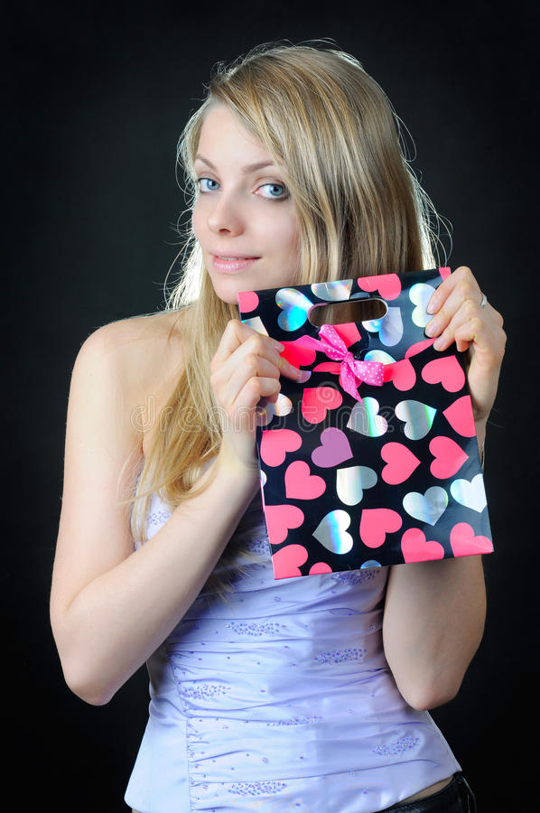 Valentine`s gift bag in hands of beautiful girl stock photography