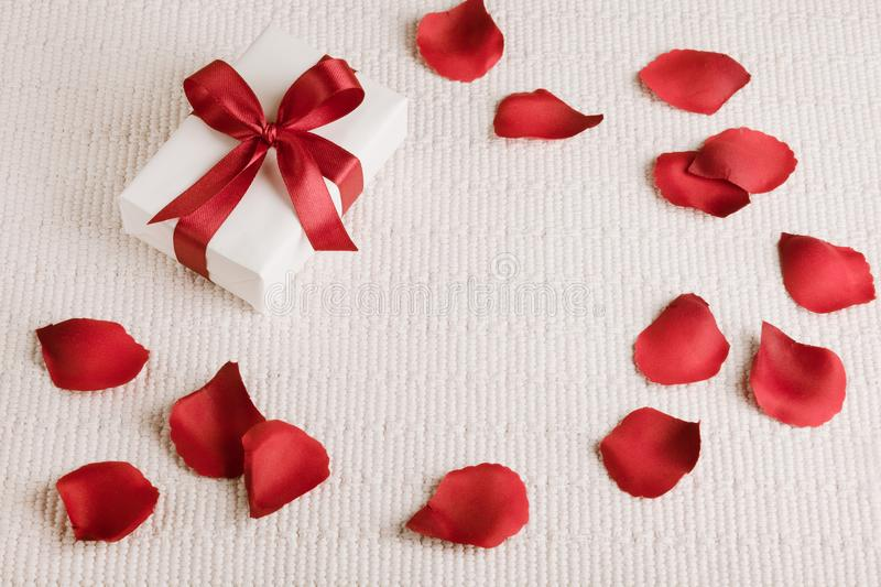 Valentine`s gift with red ribbon and red rose petals. royalty free stock photos