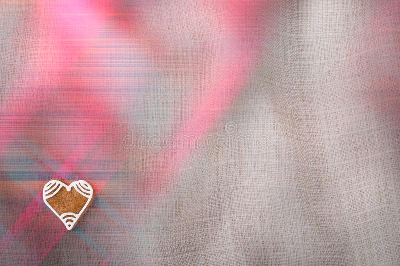 Valentine`s gingerbread heart for good luck on crumpled textile stock photos