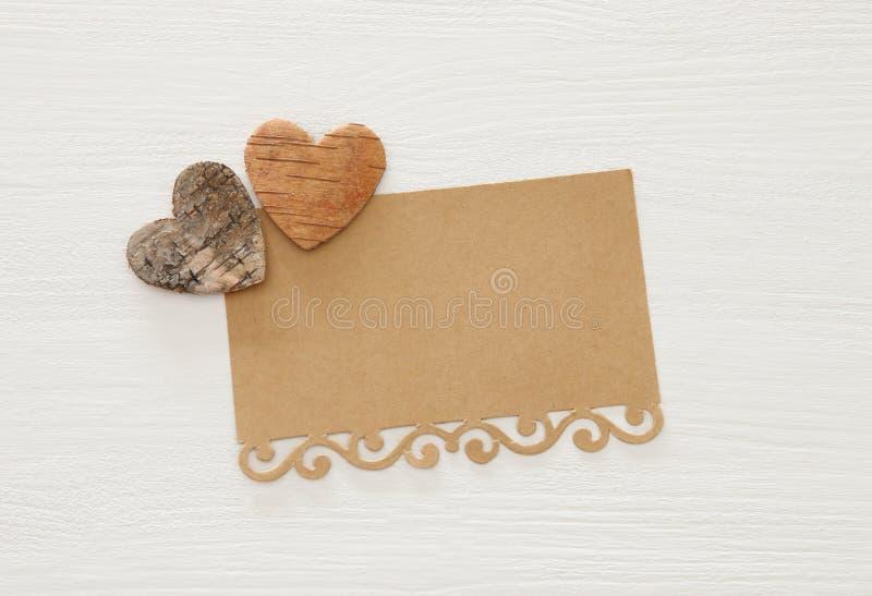 Valentine& x27; s-Tageskonzept Herzen cutted vom Baumstamm und von der Weinlesepapieranmerkung über hölzernem weißem Hintergrund lizenzfreies stockfoto