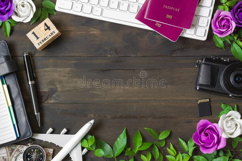 Valentine`s Travel Plan concept. Pc keyboard, passport, camera, sd card, notebook, roses, 14th February calendar box and airplan. E model. Top view with copy stock photo