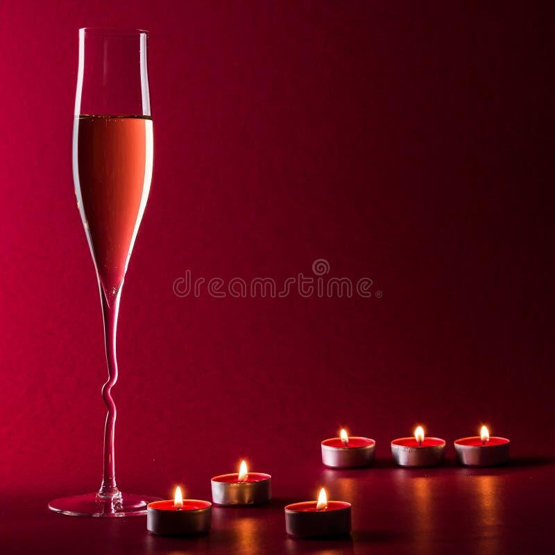 Valentine-stemming met een glas van champage en kaarsen op een rode achtergrond met vlam en brand royalty-vrije stock afbeelding