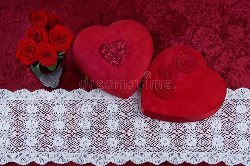 Valentine Themed Background With Heart-shaped Chocolate Box and Red Rose Bouquet on Red Crushed Velvet Background stock photos