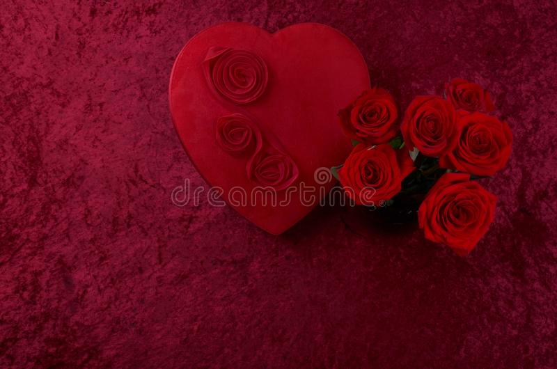 Valentine Themed Background With Red Leather Heart Shaped Chocolate Boxes And Bunch Of Roses In A Vase On Crushed Velvet Lit