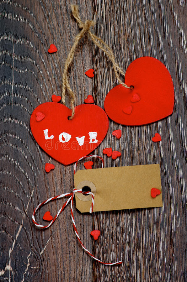Valentine. Two Red Hearts with Word Love, Blank Gift Card and Small Hearts closeup on Dark Wooden background royalty free stock images