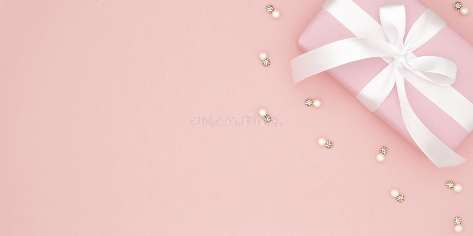 Valentine or women day pink gift with white bow ribbon on coral paper background. Concept decor love day or birthday. Flat lay. royalty free stock image