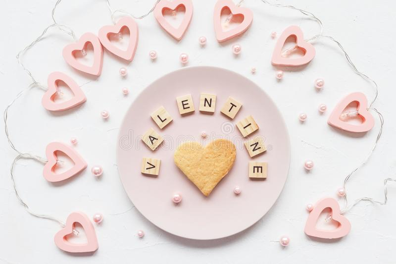 VALENTINE word and heart shaped cookie on a plate stock photo
