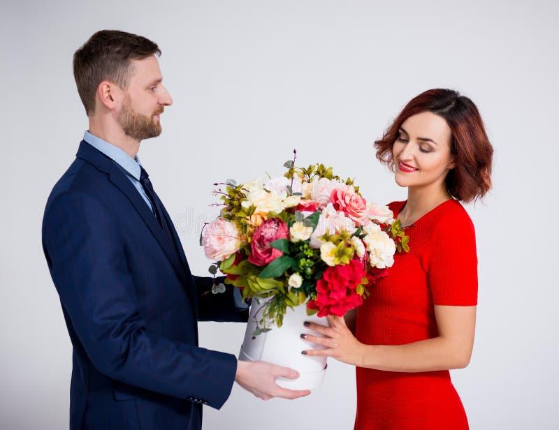 Valentiner Überraschungskonzept für Tag oder Geburtstag - ein hübscher Mann überrascht seine Freundin mit Blumen über Weiß stockfotos
