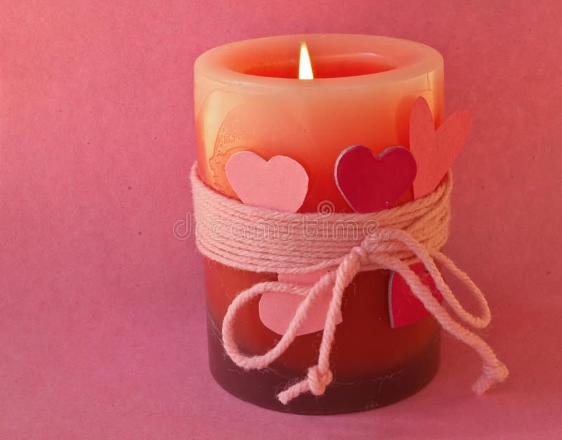 Valentines Candle. Valentine Candle with flame and hearts on a pink background royalty free stock photos