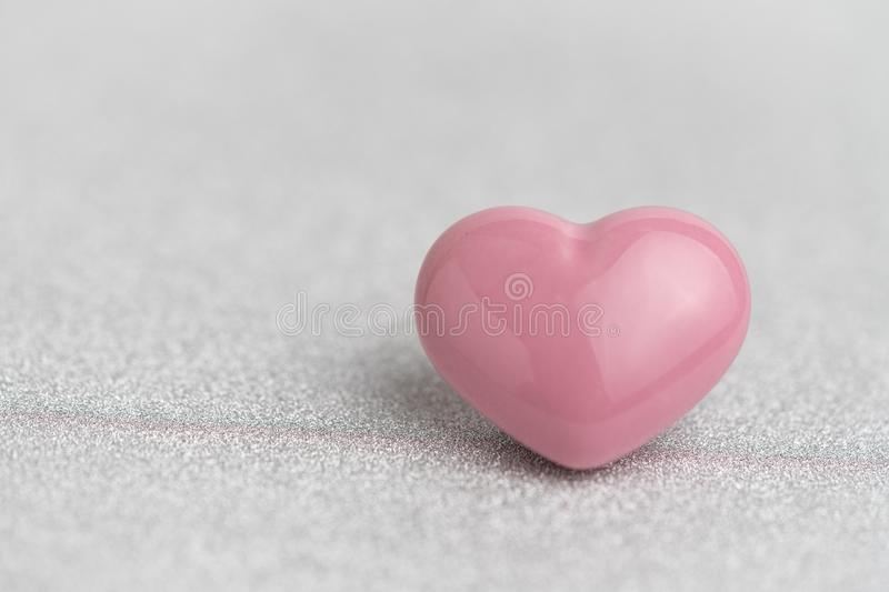 Valentines card or background with cute pink heart shape on glitter reflective particle white paper stock image