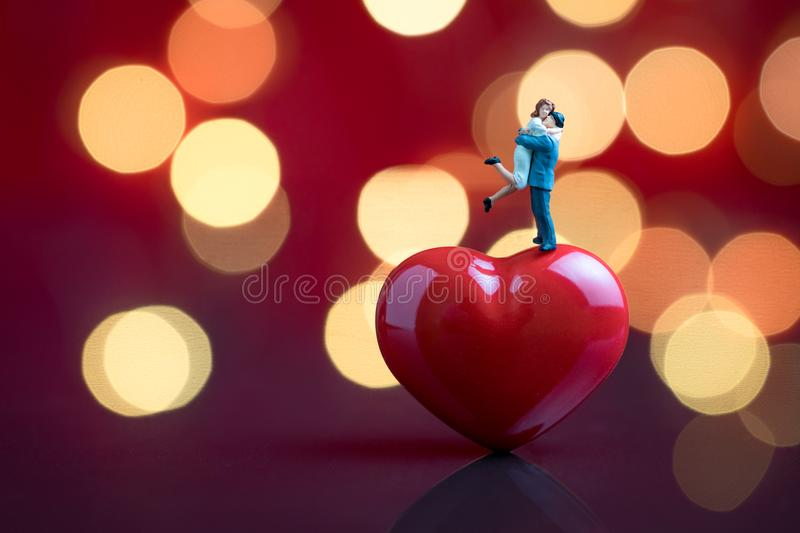 Valentines card or wallpaper with sweet miniature couple standing on red heart shape with red background and beautiful bokeh royalty free stock images