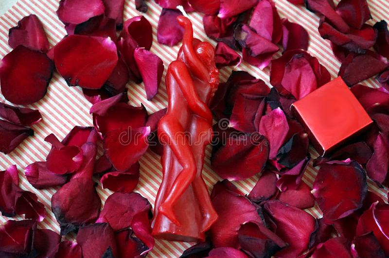 Red candle in the shape of loving couple intertwined and a jewelry gift box with rose petals on background stock photo