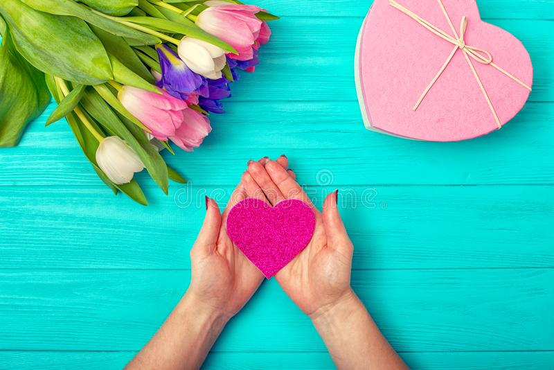 Valentines Day background with bouquet of tulips, a card with hearts and a gift.Hands of woman holding pink heart. royalty free stock photos