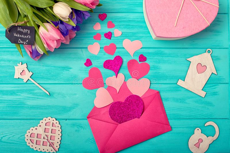 Valentines Day background with bouquet of tulips a gift and open envelope in which there are a lot of pink hearts.Happy moments. royalty free stock photos