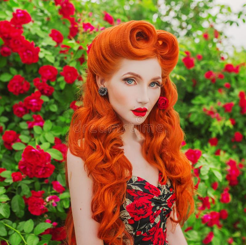 Valentines Day background. Brilliant retro girl with red lips in stylish dress with print of roses in beautiful summer garden. Red stock photography