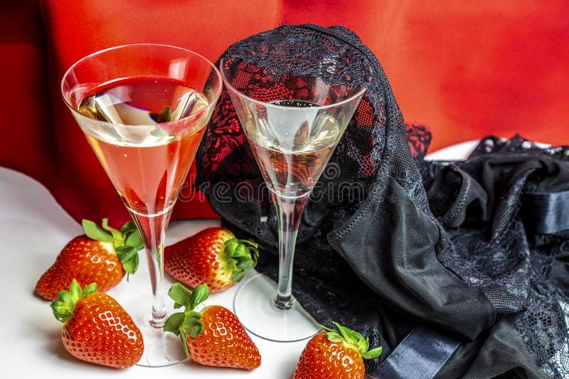 Valentines day background with champagne glasses stawberries and a lace underwear thrown on it royalty free stock photos