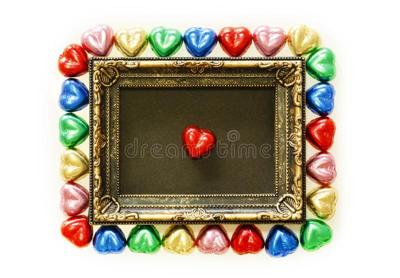 Valentines Day background with colorful chocolates heart shape and gold frame from top view. royalty free stock photos