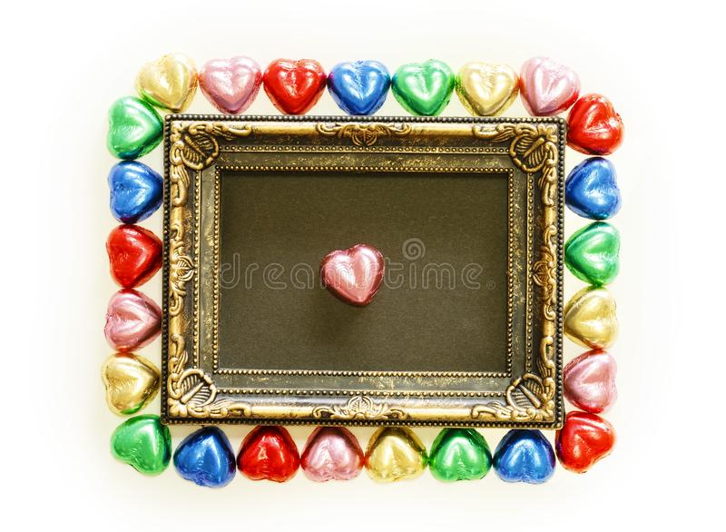 Valentines Day background with colorful chocolates heart shape and gold frame from top view. stock photography