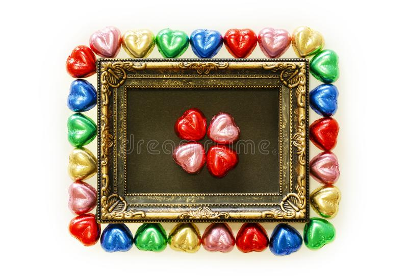 Valentines Day background with colorful chocolates heart shape and gold frame from top view. royalty free stock photography