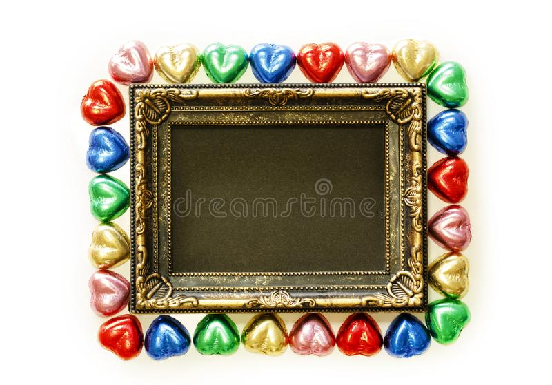 Valentines Day background with colorful chocolates heart shape and gold frame from top view. stock image