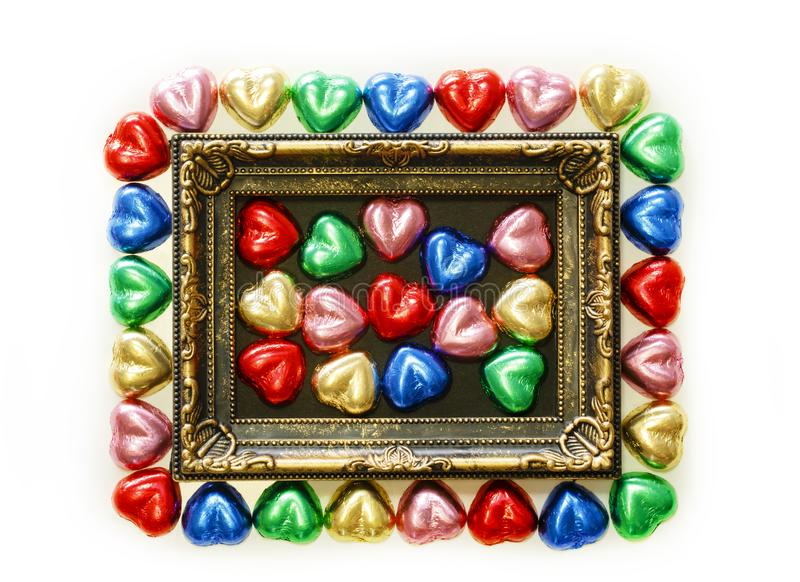Valentines Day background with colorful chocolates heart shape and gold frame from top view. royalty free stock photo