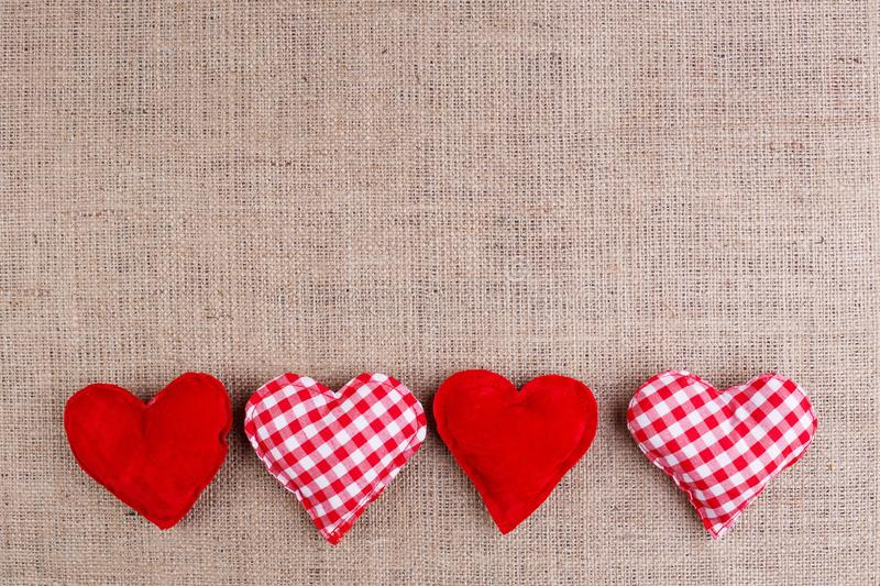 Valentines Day background with fabric hearts on sackcloth, copy stock photo