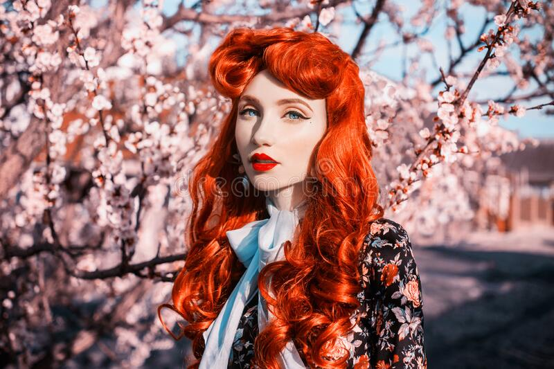 Valentines Day background. Fabulous retro girl with red lips in flower dress on awesome spring background. Spring flower. Woman stock images