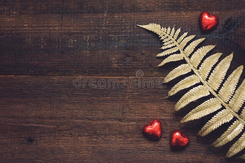 Valentines Day background, mockup with red heart shape chocolate candies and golden leaves on wooden background. Valentine Day, royalty free stock image