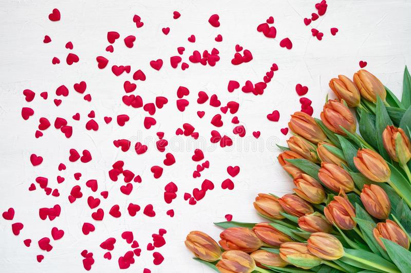 Valentines Day background. Orange tulips bouquet and red hearts on white background. Top view, copy space royalty free stock photos