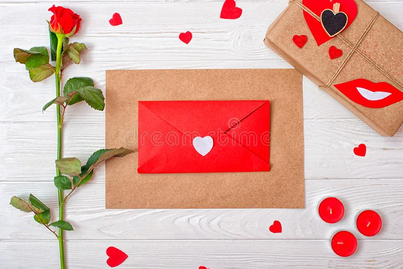 Valentines Day background with a red rose, a gift and an envelope with a heart. royalty free stock photos
